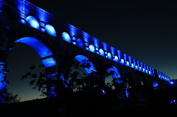 Pont du Gard lit up blue at night time